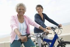 Kvinnliga vänner som rider cyklar Royaltyfria Bilder