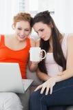 Kvinnliga vänner som tillsammans använder bärbara datorn hemma Fotografering för Bildbyråer