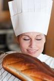 Kvinnligbagare som luktar ett bröd royaltyfri fotografi