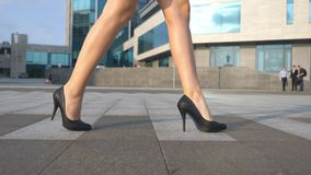 Kvinnligben i h?ga h?l skor att g? i den stads- gatan Fot av den unga aff?rskvinnan i h?g-heeled g? f?r skodon lager videofilmer