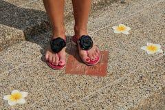 Kvinnligben i sandaler med blommor arkivbilder