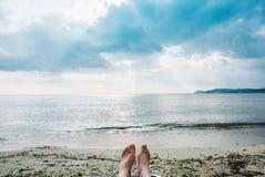 Kvinnligben och fot som solbadar på stranden Arkivbild