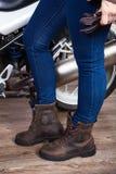 Kvinnligben som bär jeans och bruna lädersäkerhetskängor för motorcycling, är den near mopeden, övre sikt för slut Arkivfoton
