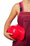 Kvinnligbyggnadsarbetare som rymmer den röda hårda hatten Arkivfoto