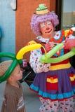 Kvinnligclownen gör ballonghatten för unge arkivbild
