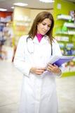 Kvinnligdoktor med förlagor inom apotek Royaltyfria Foton