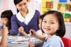 Kvinnligelev som tycker om konstgrupp i kinesisk skola Royaltyfri Bild