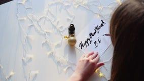 Kvinnligförlagen av bokstäver drar kortet för det nya året med färgpulver på arket, sammanträde på tabellen med girlanden i konst stock video