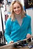 Kvinnligförsäljningar som assistenten med skidar i hyra, shoppar Arkivfoto