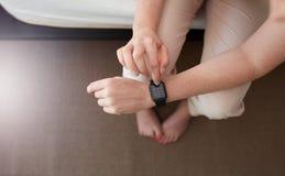 Kvinnlighänder genom att använda smartwatch arkivfoton