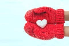 Kvinnlighänder i varma röda virkade tumvanten med snöig hjärta Whi Royaltyfri Bild