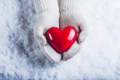 Kvinnlighänder i vit stack tumvanten med en glansig röd hjärta på en snöbakgrund Förälskelse- och St-valentinbegrepp royaltyfri bild