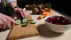 Kvinnlighänder med den bitande gurkan för kniv ombord arkivfilmer