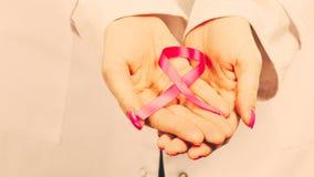 Kvinnlighänder med det rosa bandet Royaltyfri Foto