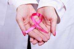 Kvinnlighänder med det rosa bandet Arkivbild