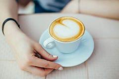 Kvinnlighänder med en cappuccinokopp i ett kafé Royaltyfri Foto