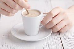 Kvinnlighänder med en cappuccinokopp i ett kafé Arkivbilder