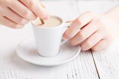 Kvinnlighänder med en cappuccinokopp i ett kafé Royaltyfria Bilder