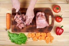 Kvinnlighänder med en kniv, snitt köttet på träbrädet Sunt äta och livsstil arkivfoto