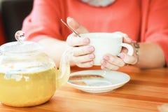 Kvinnlighänder med en kopp av varmt te för förkylning och temperatur Aro arkivbild
