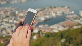 Kvinnlighänder med en smartphone Använd telefonen mot bakgrunden av staden av Bergen stock video
