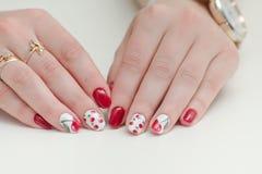 Kvinnlighänder med manikyr som är röd spikar polermedel som drar med körsbär Vit bakgrund Royaltyfri Fotografi