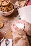 Kvinnlighänder med varma drink- och chokladkakor Royaltyfri Foto