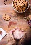Kvinnlighänder med varma drink- och chokladkakor Royaltyfri Fotografi