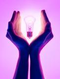 Kvinnlighänder och lysande ljus kula för innehav Elektrisk glödande ljus kula i hand på purpurfärgad bakgrund Inspirationidéer lu Fotografering för Bildbyråer