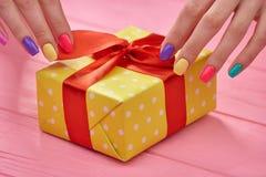 Kvinnlighänder som packar upp gåvaasken Arkivbild