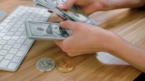 Kvinnlighänder som räknar kassa med bitcoins Skördsikten av kvinnan räcker att räkna den stora packen av dollarsedlar på trä stock video