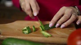 Kvinnlighänder som skivar gurkan på skärbräda lager videofilmer