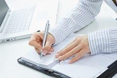 kvinnlighanden bemärker writing Arkivbild
