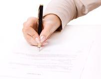 Kvinnlighanden som undertecknar ett avtal, intecknar Arkivbild