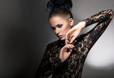 Kvinnlighet. Attraktiv stiliserad kvinna i svart klänning med Pilbåge-fnuren. Neatness Arkivbild