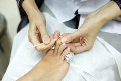 Kvinnlighänder, det rengörande fingret spikar av kvinnafot Royaltyfri Foto