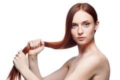 Kvinnligholding henne långt ursnyggt naturligt rött hår royaltyfri foto