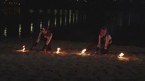Kvinnligjonglörer som lyfter tända facklor som ligger på sand lager videofilmer