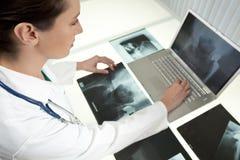 Kvinnligkvinnadoktor Looking på röntgenstrålar & bärbar dator Arkivbilder