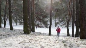 Kvinnliglöpare som rustar i den kalla vinterskogen som slitage varma sportiga running kläder och handskar lager videofilmer