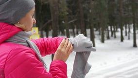 Kvinnliglöpare som rustar i den kalla vinterskogen som slitage varma sportiga running kläder och handskar stock video