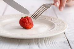 Kvinnlign äter en ny jordgubbe med gaffeln Arkivbild