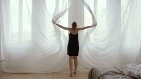Kvinnlign öppnar gardinultrarapiden arkivfilmer