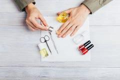 Kvinnlign applicerar att uppföda olja på nagelband royaltyfria foton