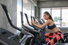 Kvinnlign cyklar i idrottshallen Stående av flickan som övar på cardio maskiner i sportklubban Nätta kvinnor förkroppsligar byggm arkivfoton