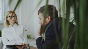 Kvinnlign erfor psykologen som talar och lyssnar till den upprivna affärsmanpatienten och skriver anmärkningar på skrivplattan i  lager videofilmer