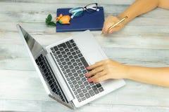 Kvinnlign för affärskvinnan räcker arbete på den lantliga trätabellen på la arkivfoto