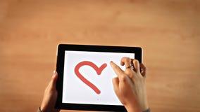 Kvinnlign för den bästa sikten räcker minnestavlan för teckningshjärtaom lager videofilmer