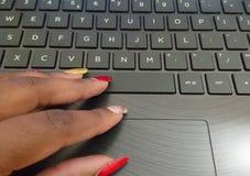 Kvinnlign fingrar visat genom att använda tangentbordet arkivbild