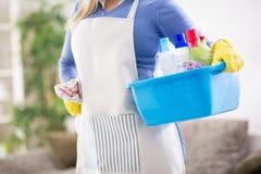 Kvinnlign förbereder kemiska produkter för rengörande hus Arkivbild